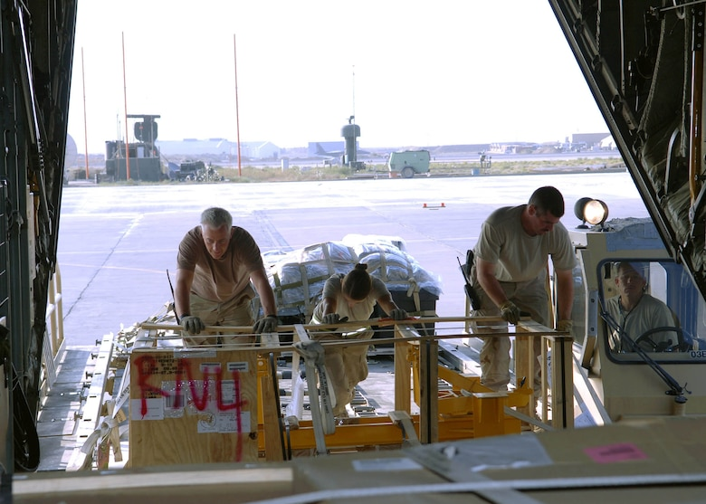 Senior Airman Sarah Hansen (middle), 67th Expeditionary Aerial Port Squadron, helps other members of her squadron push pallets from the loader into the cargo area of a C-130. Airman Hansen is a reservist deployed from Hill Air Force Base, Utah. (U.S. Air Force photo by Staff Sgt. Craig Seals)