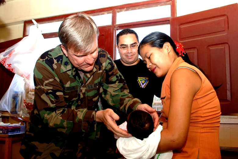 Lt. Col. Mark Desjardins, from the143rd Medical Group in Quonset Point, R.I., and Tech. Sgt. Juan Hernandez, from the 163d RW Medical Group, treats a newborn Bolivian boy during a Medical Readiness Training Exercise in Cobija, Bolivia.  (U.S. Air Force photo)