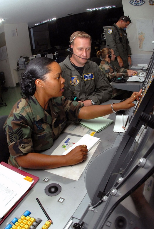 Tech. Sgt. Connie Brent and Maj. Charles Dennison control a large force exercise using the Base Air Defense Ground Environment system at Naha Air Base, Japan. Sergeant Brent relays time-sensitive information to Major Dennison, the mission crew commander, who controls the air space by guiding aircraft into different sections according to the mission plan. They are assigned to the 623rd Air Control Flight. (U.S. Air Force photo/Staff Sgt. Steven Nabor)
