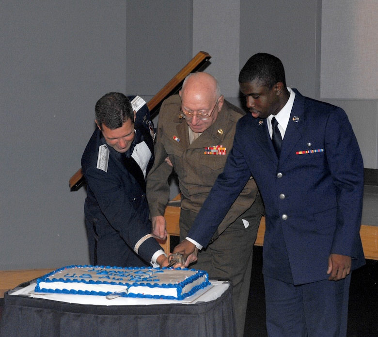"WHITEMAN AIR FORCE BASE, Mo. -- Left to right: Brig. Gen. Greg Biscone, 509th Bomb Wing commander, retired Chief Master Sgt. Mel Bockelman and Airman Basic James Williams, 509th Medical Support Squadron, cut the cake at the Air Force Ball Aug. 18. It is an Air Force tradition to have the most senior ranking Airman and the youngest Airman cut the cake. Chief Bockelman is wearing his Army Air Corps Class ""A"" uniform with the Eisenhower battle jacket, which was designed by Gen. Dwight D. Eisenhower during World War II. This year's ball commemorated the Air Force's 60th Anniversary, and was held at Elliott Union on the University of Central Missouri campus. (U.S. Air Force photo/Tech. Sgt. Samuel Park)"