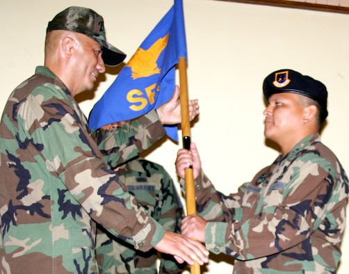 ANDERSEN AIR FORCE BASE, Guam - Capt. Joseph Pangelinan takes the guidon 254th Security Forces Squadron guidon from Col. James Montague, 254th Air Base Group commander, during his change of command ceremony.  Captain Pangelinan became commander of the 254th SFS in a change of command ceremony held Aug. 11 at the Oceanview Conference Center.  (Photo by Senior Airman Christine Martinez/Guam Air National Guard)