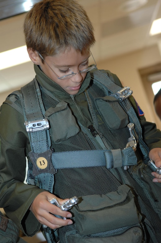 Ten-year-old Brandon Smalling tries on life support gear, Thursday August 10 at the 357th Fighter Squadron at Davis-Monthan AFB, Ariz as part of the Pilot for a Day program. The program is designed to help children with disabilities or serious illnesses to enjoy a day focused on them and their interest in aviation. Activities in the program include; trying on life support equipment, using Night Vision goggles, flying an A-10 simulator, and seeing an A-10  up close.(U.S. Air Force photo/Senior Airman Christina D. Ponte)