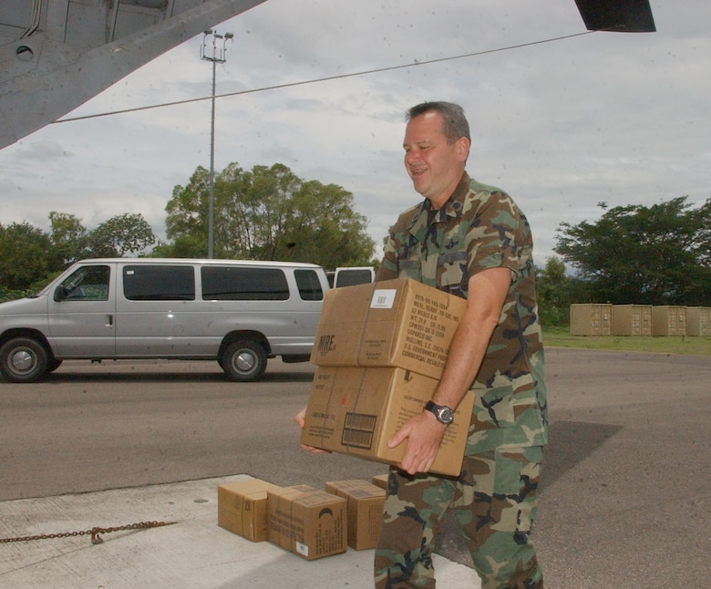 Air Force Lt. Col. Randall Vogel loads meals ready to eat onto a CH-47 Chinook helicopter Aug. 21 for troops deploying from Honduras.  Approximately 25 Airmen and Soldiers from Soto Cano Air Base left Honduras to assess the damage caused by Hurricane Dean in Belize and assist Belize in recovery efforts.  U.S. Air Force photo by Martin Chahin.