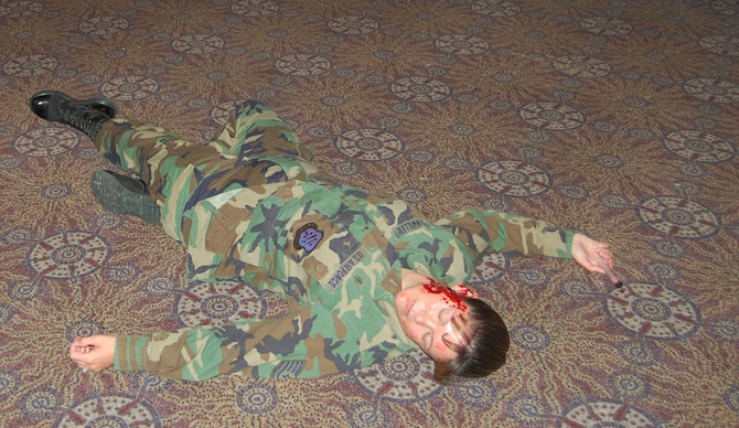 """The """"hostage taker"""" from the exercise lies mortally wounded on the base auditorium floor after the hostage situation. Moulage, make-up applied to look like an injury, was used to make the scenario as realistic as possible. (U.S. Air Force photo by Corey Dahl)"""