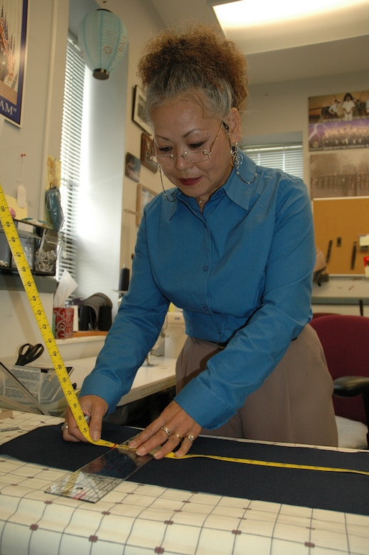 Chizuko Lowman measures the hemline on a pair of trousers. (U.S. Air Force photo by William J. Sharp)