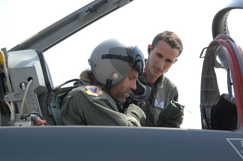 "WHITEMAN AIR FORCE BASE, Mo. – Left to right: Country music performer ""Big Kenny"" part of the duo that makes up Big & Rich gets strapped in a T-38 as he receives a pre-mission briefing from Capt. Richard Lyons, 394th Combat Training Squadron, in preparation for an incentive flight Aug. 16. The Big & Rich members, who have demonstrated their support for the military at numerous public concerts and events, got a chance to say ""Thank you,"" to troops and recognize them for their service during a forum in the roll call room. (U.S. Air Force photo/Senior Airman Lauren Padden)"