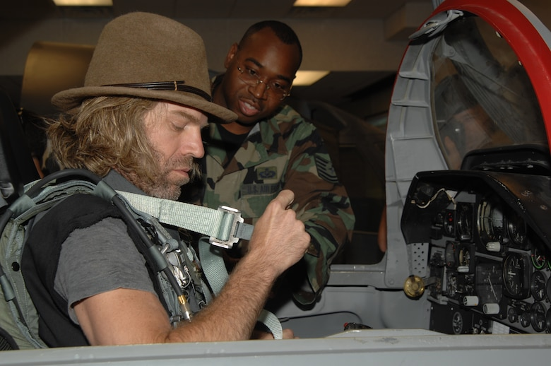 "WHITEMAN AIR FORCE BASE, Mo. – Left to right: Country music performer ""Big Kenny,"" part of the duo who make up Big & Rich, sits in a T-38 trainer while Tech. Sgt. Victor Ware, 509th Operations Support Squadron assists him Aug. 16. The Big & Rich members, who have demonstrated their support for the military at numerous public concerts and events, got a chance to say ""Thank you,"" to troops and recognize them for their service during a forum in the roll call room. (U.S. Air Force photo/Senior Airman Lauren Padden)"
