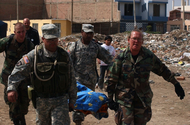 From left, Senior Airman Shaun Emery, Army Specialist Jose Hernandez, Army Lt. Col. Eduardo Zarzabal and Tech. Sgt Mellisa Walker, from the Joint Task Force-Bravo medical humanitarian relief team, carry a woman from her home to the site of the team's medical care site. The task force deployed Aug. 17 to provide medical humanitarian assistance to the citizens of Pisco, Peru following an 8.0 magnitude earthquake Aug. 15. U.S. Army photo by Specialist Grant Vaught.