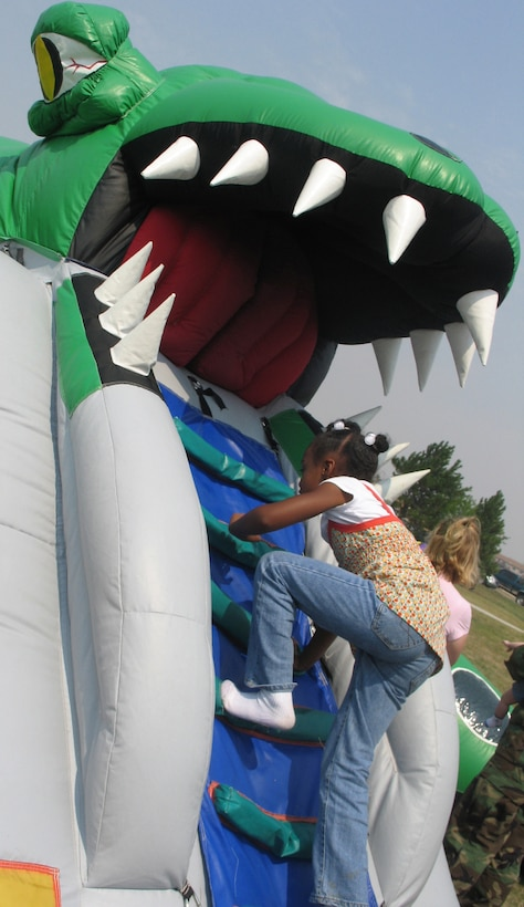 The daughter of an Ellsworth Airman braves the climb into the mouth of an inflatable dragon that housed a maze of activity during the Ellsworth base picnic Aug. 20. This annual family-friendly event was sponsored primarily by local businesses as a way to say thank you to active-duty Airmen, retirees, Department of Defense civilians and families for their hard work, dedication and sacrifices. (U.S. Air Force photo/Staff Sgt. Shanda De Anda)