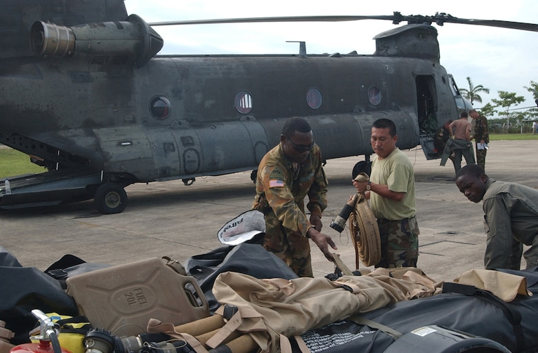 BELIZE CITY, Belize ? Army Sgt. Barry Baptiste, a fuels specialist assigned to the 1st Battalion, 228th Aviation Regiment at Soto Cano Air Base, Honduras, loads cargo onto a trailer with the help of soldiers from the Belizean Defense Force here Aug. 21.  Sergeant Baptiste, a native of Brooklyn, N.Y., is here with a team of approximately 20 U.S. Soldiers and Airmen serving on an initial assessment team following the landfall of Hurricane Dean.  (U.S. Air Force photo by Tech. Sgt. Sonny Cohrs)