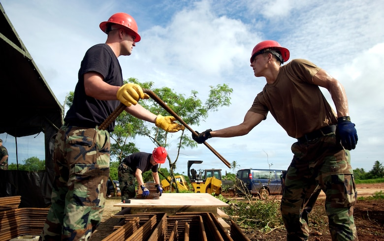 ANDERSEN AFB, GUAM - Staff Sgt. Jeremy Reneau passes a piece of rebar to Airman 1st Class Christopher David, 554th RED HORSE Squadron, at Northwest Field, Aug. 22, 2007.  The 554th RED HORSE Squadron is currently building new infastructure on Northwest Field. (Photo by Senior Airman Miranda Moorer/36th Wing Public Affairs)