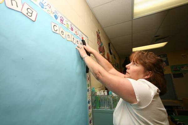 Marilyn Skipper a Pre-kindergarten 3 teacher at Lackland Elementary on Lackland Air Force Base, Texas, decorates her classroom bulletin board Aug. 17 in preparation for the upcoming school year. Classes are scheduled to begin on base Aug. 27. (USAF photo by Robbin Cresswell)