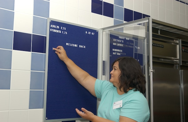 Leonorilda Carrillo prepares the Stacey Junior/Senior High school's cafeteria menu board Aug. 20. Permission was granted on Aug. 16 for off-base military children to attend Lackland ISD schools because of declining enrollment numbers due to North Wherry housing closure. (USAF photo by Alan Boedeker)