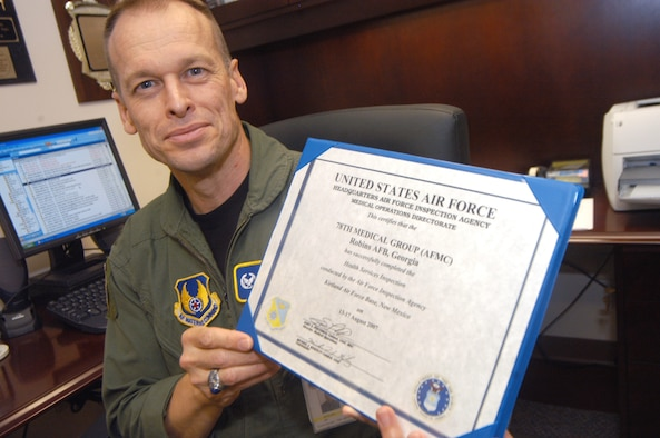 Col. Jim McClain, 78th Medical Group commander, shows off the Health Services Inspection certificate from the Air Force Inspection Agency.  U. S. Air Force photo by Sue Sapp