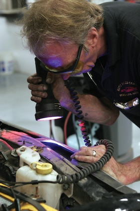 Duane Dramen, a mechanic at the station?s Auto Service Center, uses a black light to check the Freon lines for leaks after mixing dye in with the Freon, here Aug. 22.