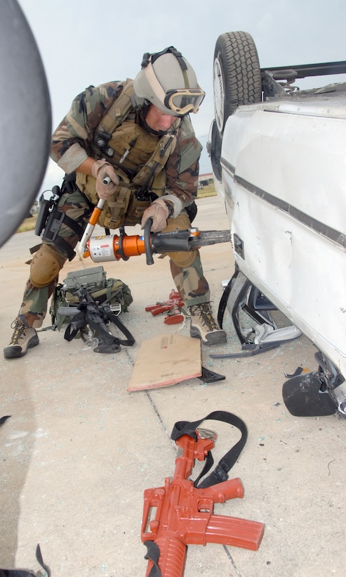 """Air Force Reservist Master Sgt. James """"JJ"""" Johnston, 308th Rescue Squadron, pararescueman. uses the jaws of life to extract casulaties from a overturned vehicle during training at Patrick Air Force Base, Fla. The PJs were performing casualty assessment and extraction from a simulated improvised explosive device, or IED, attack on a convoy of vehicles Aug. 23. (Air Force photo/Master Sgt. Chance C. Babin)"""