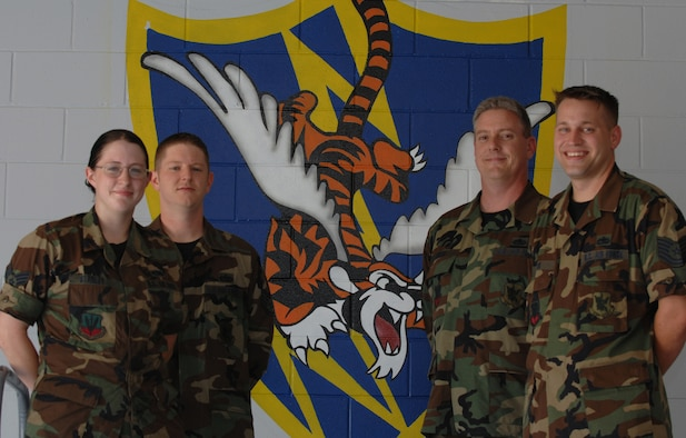 (From left to right) Senior Airman Amanda Stanley, Staff Sgt. Christopher Russell, Tech. Sgt. Patrick Smith, and Tech. Sgt. Jeremy Fisk, 723rd Maintenance Squadron fabrication flight metals technicians, stand before one of seven murals painted on volunteer time over a period of three months. (U.S. Air Force photo by Airman 1st Class Brittany Barker)