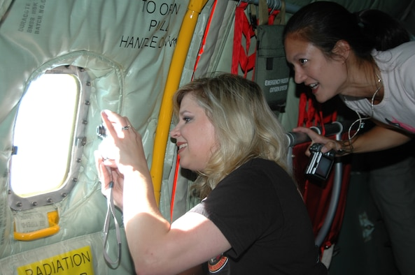 Two Ellsworth spouses take pictures of a B-1 through the window of a KC-135 during an incentive flight Aug. 9. During the flight, the spouses were able to view a refueling procedure from the boom pod of the tanker.