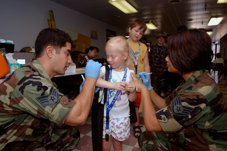 This won't hurt. Audrey Houser, daughter of  deployed member Lt Col Rodney Houser, getting her shots from Staff Sgt. Francisco Torres and Staff Sgt. Allita Romero. (Photo by Paul Testerman)