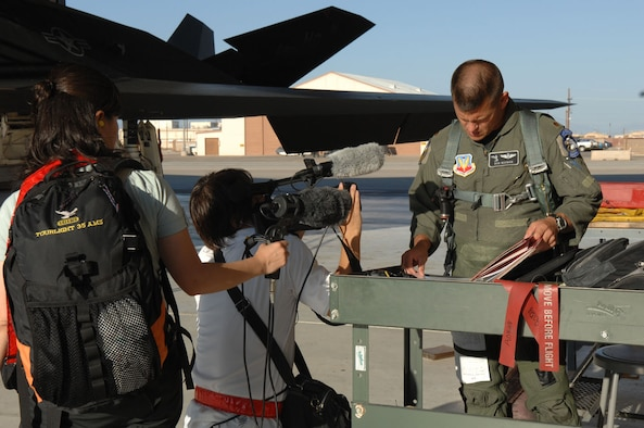 Cameraman and woman Chisato Okuma and Ryichi Takano from NTN television broadcasting station in Tokyo, Japan document Maj. Robert Nooman, 49th Fighter Wing chief of safety Aug. 27. Ryichi Takano and Chisato Okuma were at Holloman and Nellis Air Force Base documenting the history of the F-117 and its retirement. Also the crew follwed around Major Nooman for a day to capture the day in the life of a pilot in the U.S. Air Force. (U.S. Air Force photo/Senior Airman Anthony Nelson)