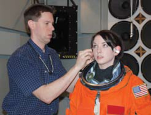 General Dynamics Advanced Information Systems (GDAIS) technician Paul Schley fits miniature microphones in the ears of test subject Beth Greschner, also of GDAIS.  The microphones record sound levels equivalent to those experienced by astronauts during space shuttle liftoff (photo by Chris Gulliford, AFRL Human Effectiveness Directorate).