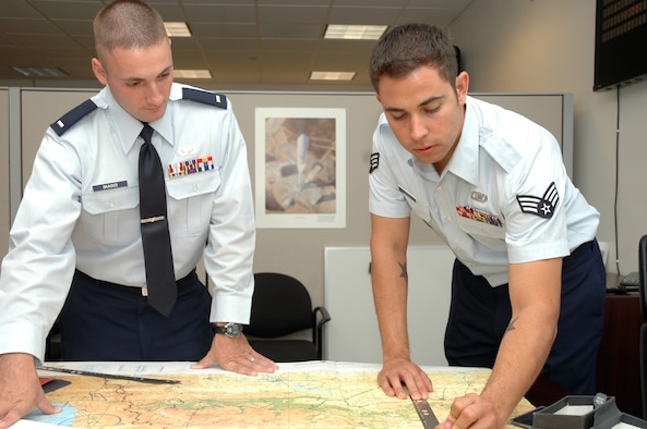 Senior Airman Chris Szopa, a 30th OSS Intelligence Flight intelligence analyst, shows his commander, 1st Lt. Ryan Skaggs, the location of a intelligence operation. Working with maps and the terrain of certain locations is a small portion of the intelligence gathering process.