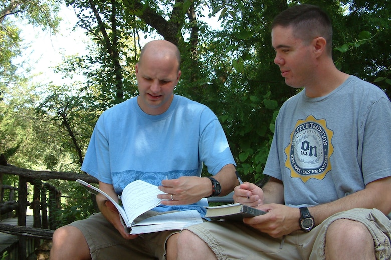 MCCONNELL AIR FORCE BASE, Kan. – Chaplains (Capts.) Travis Sears and Kevin Hudson review the songs for worship service during the 22nd Maintenance Group reunion and reintegration retreat at the Rock Springs 4-H Center, near Junction City, Kan., Aug. 26. More than 70 military members, some recently returned from deployment, and their families participated in the event. (U.S. Air Force photo by Tech. Sgt. Chyrece Campbell)
