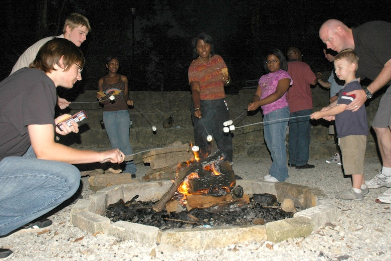 MCCONNELL AIR FORCE BASE, Kan. – Team McConnell members roast marshmallows in a fire camp during the 22nd Maintenance Group Reunion and Reintegration Aug. 25 at the Rock Springs 4-H Center, near Junction City, Kan. Archery, horseback riding, trap and rifle shooting were among some of the activities retreat members could participate in. The day's activities ended with a camp fire. More than 70 military members, some recently returned from deployment, and their families participated in the event. (U.S. Air Force photo by Tech. Sgt. Chyrece Campbell)