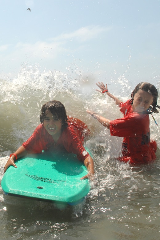 Robert McIntosh rides a wave on a boogie board while his friend, Katie, tries not to get splashed by the incoming wave during the Youth Summer Camp trip to Seal Beach, Aug 22. (Photo by Stephen Schester)