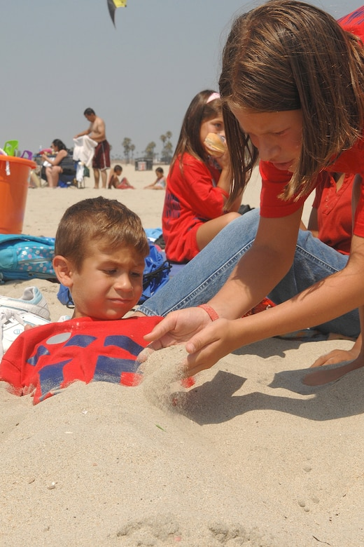 Sky Ochoa buries her brother, Zachery in the sand during the Youth Summer Camp trip to Seal Beach, Aug 22. (Photo by Stephen Schester)
