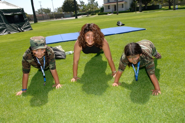 Ashley, Elma and Alexandria Lopez, daughters of Tech Sgt. Attilio Lopez, demonstrate push-ups.  (Photo by Paul Testerman)