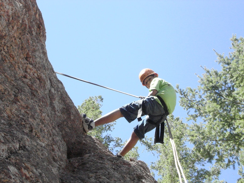 Ryan Gonzalez rappels down a cliff face at Big Rock Creek Adventure Camp in Valyermo, Calif. Youth Center children visited Big Rock Creek as part of an Edwards Youth Center summer camp. The center's before and after program provides activities during the summer such as bowling, swimming, summer camp and amusement park trips.  (Photo by Sharon Harmon)