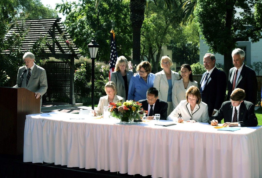 Sacramento County Supervisor Roger Dickinson (left) reads the ceremonial scroll Aug. 27 at the former McClellan Air Force Base in California. The ceremony marked the first time in the nation the military funded an early transfer with privatized remediation at a National Priority List site. Copies of the scroll are signed by (from left, front row): Linda Adams of the California Environmental Protection Agency, Kieth Takata, EPA Region 9, Kathryn Halvorson of the Air Force Real Property Agency, Don Nottoli of the Sacramento County Board of Supervisors, and (from left, back row): Pamela Creedon of the California Regional Water Quality Control Board, Maureen Gorsen of the California Department of Toxic Substances Control, Kathleen Johnson and Yvonne Fong of the EPA Region 9, Phil Mook of the  AFRPA, and Rob Leonard of the Sacramento Department of Economic Development. (U.S. Air Force photo)