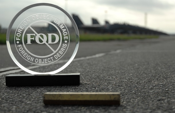 The Golden Bolt sits next to a foreign object damage plaque on the RAF Lakenheath flight line Aug. 30. If anyone finds the bolt lying around and picks it up, they get a day pass amongst other goodies from the FOD Prevention Incentive Program. (U.S. Air Force illustration by Airman 1st Class Jessica Snow.)