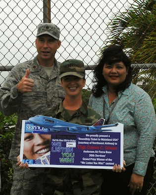 "Out of six grand prize winners in the Pacific Air Forces who participated in the ""We Listen, You Win"" Services command-wide comment card promotion, Tech. Sgt. Coleen Gibson, 36th Wing, was one of the lucky winners to win roundtrip airline tickets to travel to any destination in the U.S.  The award was presented to her by Maj. Alex Gaines, 36th Services Squadron commander, and Marie Lizama, Northwest Airlines representative, on Nov. 28.  (U.S. Air Force photo/Angelica Covington)"