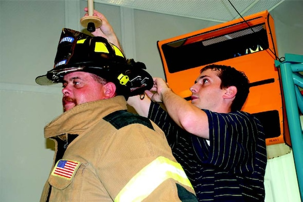 Anthropometry specialist Mark Boehmer (right), of General Dynamics Advanced Information Systems, prepares firefighter Paul Bauer, a 19-year veteran and part-time firefighter engineer with the city of Mason (Ohio) Fire Department, for a three-dimensional scan dressed in full turnout gear (photo by AFRL's Chris Gulliford).