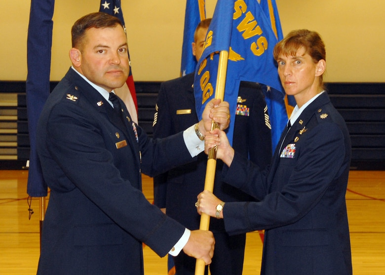 BUCKLEY AIR FORCE BASE, Colo. -- Col. Christopher Ayres, 460th Operations Group commander, passes the 11th Space Warning Squadron guidon to Lt. Col. Holly Weik, 11th SWS commander, symbolizing the activation of the 11th SWS. On Dec. 3, the 460th OG, Det. 1, stood down as the 11th SWS stood up in a ceremony held at the Buckley Fitness Center. (U.S. Air Force photo by Airman 1st Class Alex Gochnour)