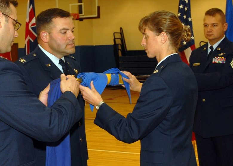 BUCKLEY AIR FORCE BASE, Colo. -- Lt. Col. Holly Weik, 11th Space Warning Squadron commander, and Col. Christopher Ayres, 460th Operations Group commander, furl the guidon of the 460th Operations Group, Detachment 1, to symbolize the de-activaion of the detachment. On Dec. 3, the 460th OG, Det. 1, stood down as the 11th SWS stood up in a ceremony held at the Buckley Fitness Center. (U.S. Air Force photo by Airman 1st Class Alex Gochnour)