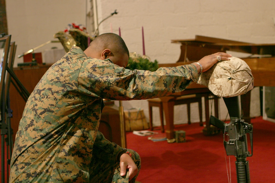 A Marine from 2nd Assault Amphibian Battalion, 2nd Marine Division, II Marine Expeditionary Force, pays his final respects to four fallen Marines during the battalion?s memorial service at the Protestant Chapel here Dec. 6. The Marines honored in the ceremony were Cpl. Christopher R. Degiovine, assault amphibian vehicle crewman, Company A; Cpl. Derek C. Dixon, a data technician with Co. A; Cpl. Willie P. Celestine; a radio operator with Co. A; and Cpl. Reynold J. Armand, a food service specialist with Headquarters & Service Company. They all gave their lives in support of Operation Iraqi Freedom. (Official Marine Corps Photo by Lance Cpl. Christopher Zahn) (Released)