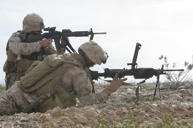 Cpl. Kyle Blades, team leader, 1st squad, 2nd platoon, Fox Company, 2/24, provides covering fire for Lance Cpl. Matt Shimon, SAW gunner, 2nd platoon, Fox Company, 2/24, while he reloads his weapon.