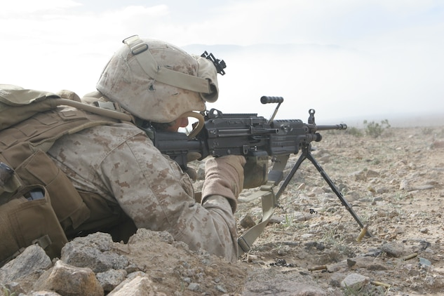 Lance Cpl. Matt Shimon, SAW gunner, 1st squad, 2nd platoon, Fox Company, 2/24, cuts through the smoke of an aircraft, artillery and mortar bombardment with rounds from his SAW.