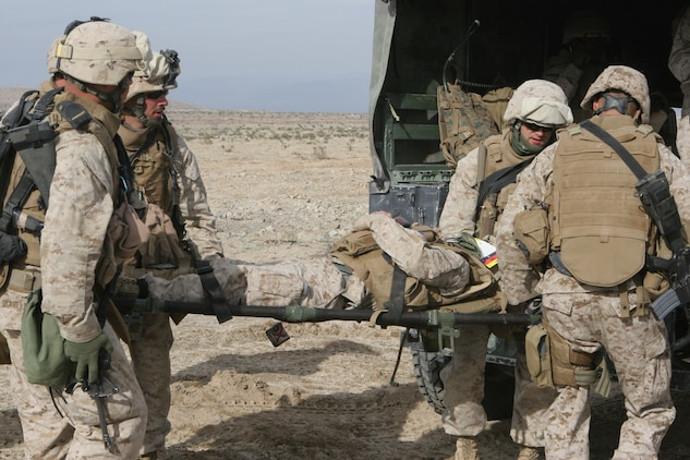 The Marines and sailors of 2nd platoon?s aid and litter team evacuate a casualty into the back of a vehicle.