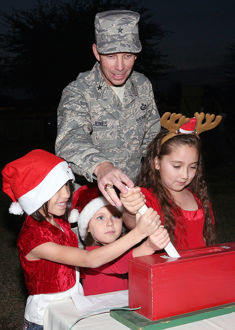 Brig. Gen. Darrell Jones, former 37th Training Wing commander at Lackland Air Force Base, Texas, gets a little assistance throwing the switch on the Christmas tree lights from members of the Chapel Children's Choir at the Gateway Club on Nov. 29, 2007. The annual Christmas Tree Lighting also featured the Air Force Band of the West and included a visit from costumed North Pole characters. (USAF photo by Robbin Cresswell)
