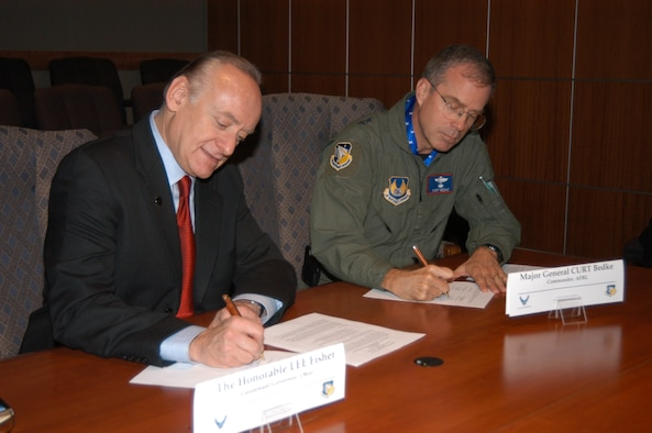 Lt. Governor Lee Fisher and Air Force Research Laboratory commander Maj. Gen. Curtis Bedke, sign the Memorandum of Understanding which will encourage collaboration for Air Force research and economic growth. (Air Force photo by Jeremy Patton)