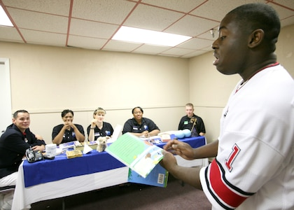 In a Bill Cosby impression, Senor Airman Jonathan Allen reads from a children's book to a panel during the Air Force World Wide Talent Contest at Lackland Air Force Base, Texas. Airman Allen, from F. E. Warren Air Force Base, Wyo., is a trumpet player and is competing for a spot on the 2008 Tops in Blue team. The competition, held Dec. 2-10, is the first step to Tops in Blue.  (U.S. Air Force photo/Robbin Cresswell)