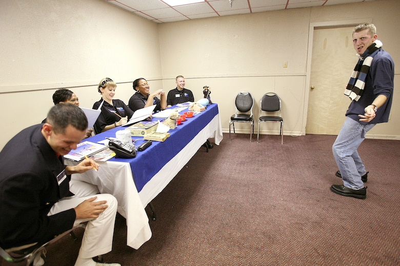 """Airman 1st Class Brian Carmack solicits a laugh from a panel of judges during a comedy routine in the """"specialty"""" audition during the Air Force World Wide Talent Contest held at Lackland Air Force Base, Texas, from December 2-10. The five-person panel of current and former Tops in Blue judges are (from left) Staff Sgt. Daniel Rutherford, Fort Meade, Maryland; Staff Sgt. LaTanza Meabon-Whiteside, Little Rock AFB, Ark.; Staff Sgt. Amber Young, Offutt AFB, Neb.; Staff Sgt. Tatenisia Stirrup, Tinker AFB, Okla.; and Senior Airman Bryce Zabric, Dyess AFB, Texas. World Wide is the first step to Tops in Blue.  Airman Carmack, a dental assistant at Lackland AFB, is competing for male vocalist for the 2008 Tops in Blue show.  (U.S. Air Force photo/Robbin Cresswell)"""