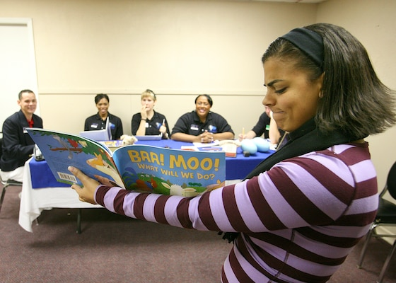 Senior Airman Shala Baugh, a linguist from Offutt Air Force Base, Neb., reads from a children's book as she tries to impress a panel of former and current Tops in Blue members. Airman Baugh is a competitor in the Air Force World Wide Talent Contest held at Lackland AFB, Texas, from Dec. 2-10.  The talent contest is the first step to Tops in Blue.  (U.S. Air Force photo/Robbin Cresswell)