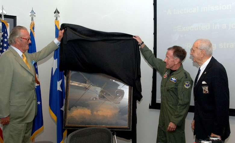 """Count Ferdinand von Galen (left) presents a limited edition painting, West Bound: A Date with the General, to Lt. Gen. Norman Seip, commander 12th Air Force and Air Forces Southern, and to Maj. Gen. (retired) David Jones, one of the original Doolittle Raiders. The painting, created by world-renowned aviation artist William S. Phillips, captures the courageous actions of the famed """"Doolittle Raiders"""" during the 1942 raid of Japan. The painting, according to Count von Galen, was donated to the James H. Doolittle Combined Air and Space Operations Center because the command embodies the character of the original Raiders in their work around the world."""