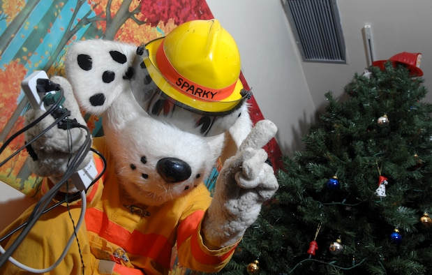 "Sparky the Fire Dog, played by Airman 1st Class Damien Montero, 36th Civil Engineering Squadron, says no to bad safety practices during the holidays. Holiday lights may look pretty, but they can also cause fires. If lights have cracked or frayed cords, throw them away. Be sure artificial Christmas trees are labeled ""flame retardant."" Water real Christmas trees several times a day. And make sure it doesn't block the room exit.   (U.S. Air Force photo/ Senior Airman Miranda Moorer)"