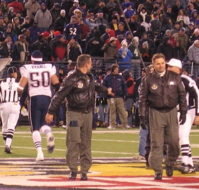 Maj. Ken Parsons, left, and Senior Master Sgt. James McKelligan, 337th Airlift Squadron, walk off the Baltimore Ravens football stadium Dec. 3 following the pre-game coin toss.